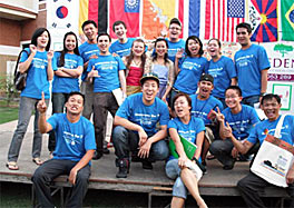 Photo of about 20 young people wearing blue T-shirts and gathered outside on a small stage. The backdrop on the stage seems to be made up of the flags of many countries.