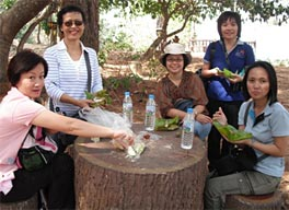 Photo of five young women sitting at a tree-stump table.