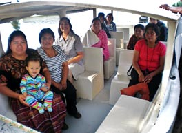 Photo of nine women sitting in a boat. The one closest to the camera holds a small boy in her lap.