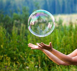 A pair of hands beneath a large bubble.