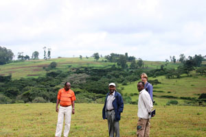 A group of people standing on a hilly grassland.