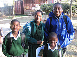 Photo of four children standing outside wearing backpacks and posing for the camera.