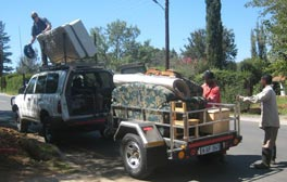 Photo of a SUV and trailer; two people load the trailer; a man stands on the roof of the car.