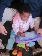 A toddler in her dad's lap on the ground, playing with a writing toy.