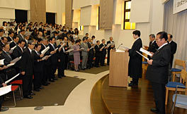 Photo of what appears to be a small auditorium or lecture hall. A man in a black robe stands a lectern. Several other men in suits stand with him facing the audience. The room appears to be full.