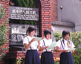 Photo of three young women standing in front of a brick memorial. They are wearing school uniforms and all are looking intently at pieces of paper that they hold in both hands. One of the young women holds a microphone in her right hand and seems to be speaking into it.