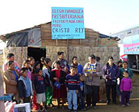 Photo of about 15 people gathered in front of a small building apparently made of woven mats and black plastic and a corrugated metal roof. A bright blue hand-lettered sign indicates that this is a Presbyterian Church.