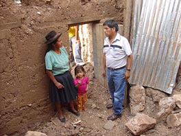 Photo of woman and a small child and a man standing next to a wall with a doorway. On the ground there is stone rubble; and corrugated metal roofing is hanging behind them.