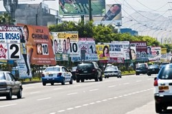 Photo of a busy street with one side completely with billboards.