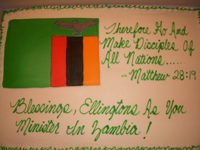 A cake with the Zambian flag and writing in green letters on white icing.