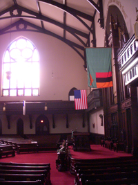 An empty church sanctuary with an American and Zambian flag hanging; an arched window behind shines light into the room.