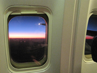 A photo of a sunrise from an airplane window.