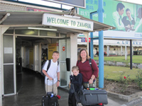 "The Ellington family (sans Dustin) standing outside of an airport with their luggage, under a sign that says ""Welcome to Zambia""; behind them is a large green billboard written in Chinese."