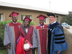 Dustin wearing an academic robe stands with three other people also wearing academic garb.