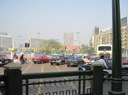 Photo of a busy street with a large building in the background.