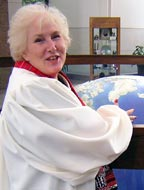 Photograph of Mary Ferris in a white clerical robe with her hands on a large globe.