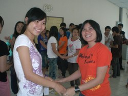 Photo of two young women apparently shaking hands.