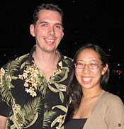 Photo of Joy Fujii and Edward Holcomb, both with large smiles, posing for the camera.
