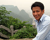 Photo of a young man smiling at the camera. In the background and below the man are mountains.