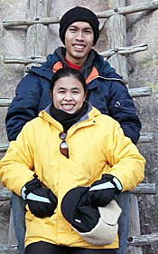 Photo of two young people dressed warmly. The young man is standing on a ladder one step above the young woman. They pose for the camera while smiling.