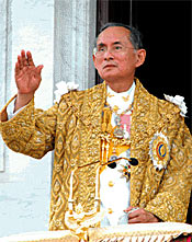 Photo of a man dressed in a white uniform and wearing a gold coat; he waves his right hand.