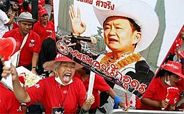 Photo a group of people wearing red shirts. One of them is holding a poster with a picture of a man wearing a cowboy hat.