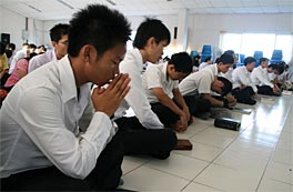 Photo of young men weating white shirts and black trousers sitting on the floor praying.