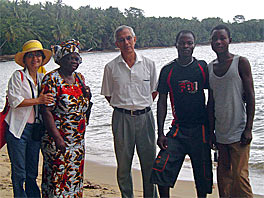 Photo of Andres and Gloria and three other people standing on a beach in a row facing the camera.