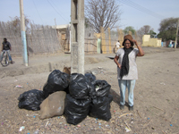 Aliamma standing by a pile of garbage bags.