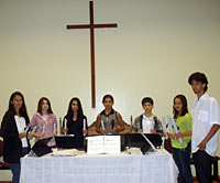 Photo of seven people standing behind a table covered in a white cloth. Behind them on the wall is a thin wooden cross.