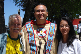 Photo of Thelma standing with two men, one of which is wearing native American clothing.