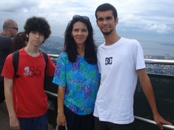 Photo of Thelma flanked by Joel and Michael; in the background is blue sky a part view of a city.