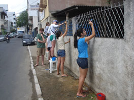 A group of youths painting a fence blue.
