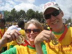 Rich and Marilyn wearing the yellow and green shirts and holding up medals.