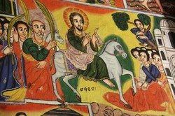 A wall painting of Jesus riding a colt surrounded by people with palm branches.