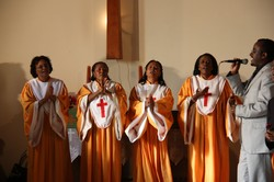 Photo of four women and a man singing; the women wear gold and white robes, the man, a suit.