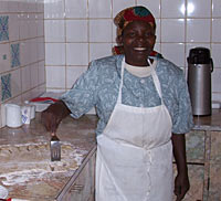 Photo of a woman standing in a kitchen. She wears an apron and holds a spatula and is smiling. Behind her, the walls are covered with square, white tile.