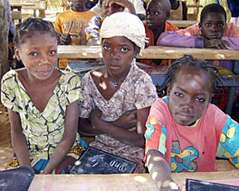 Photo of three girls about 9 years old sitting together at a desk. Other students can be seen sharing desks behind them.