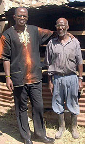 Photo of two men standing together in bright sun. Behind them appears to be a fence or corral and part of a roof.