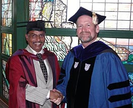 Photo of Tom shaking hands with a man; they both wear academic robes.