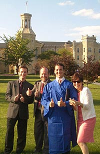 Photo of Toma and Judy with sons; Paul is wearing his graduation robe.