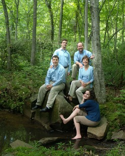Photo of the Harveys in a woods by a stream.