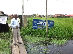 Photo of a man standing in a flooded field