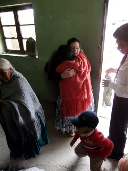Photo of a woman wearing an orange shawl hugging Sarah.
