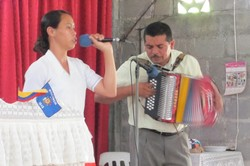 Photo of a woman holding a microphone and singing and a man playing an accordian.
