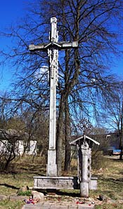 Photo of a tall stone cross. In the background are trees, buildings and a bright blue sky.