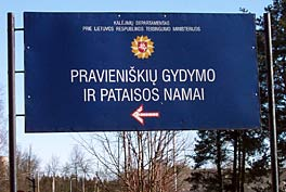 Photo of a large, dark blue, rectangular sign in Lithuanian.