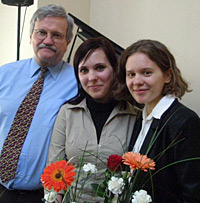 Photo of Eric Hinderliter with two young women. In the foreground is a flower arrangement.