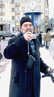Photo of Burkhard Paetzold standing in a large square in a city taking a photograph with a digital camera.