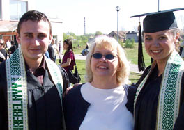 Photo of Becky Hinderliter standing between two students wearing black gowns. They are outside on a sunny day. All are smiling.